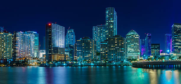 panorama of miami at night - miami stock photos and pictures