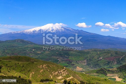 A tranquil, bucolic panorama of snowy Mt. Etna in spring, with blue sky and puffy clouds coming from the volcanic cone, and hilly green countryside in front. Shot from Troina (Enna Province). Copy space in the sky.