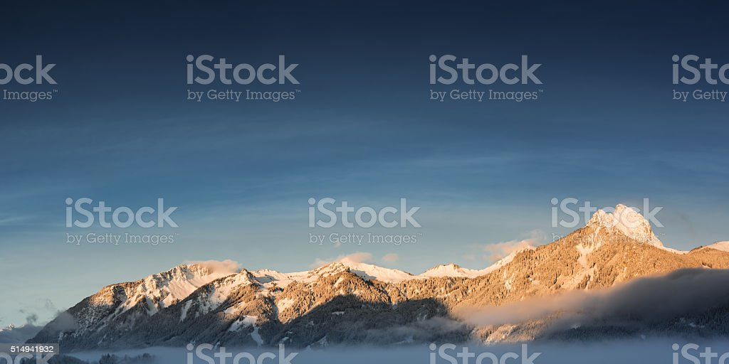 panorama of mountain chain hahnenkamm in winter at sunrise stock photo