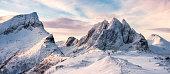 Panorama of Mountaineer standing on top of snowy mountain range at Senja, Norway