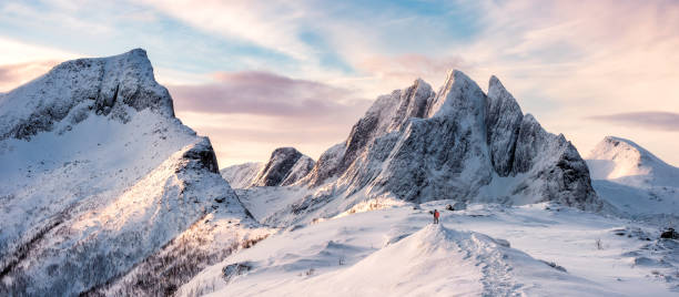 panorama of mountaineer standing on top of snowy mountain range - composizione orizzontale foto e immagini stock