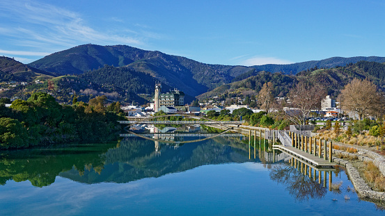 Panorama of Nelson City, reflected in the still waters of the Maitai River, New Zealand.