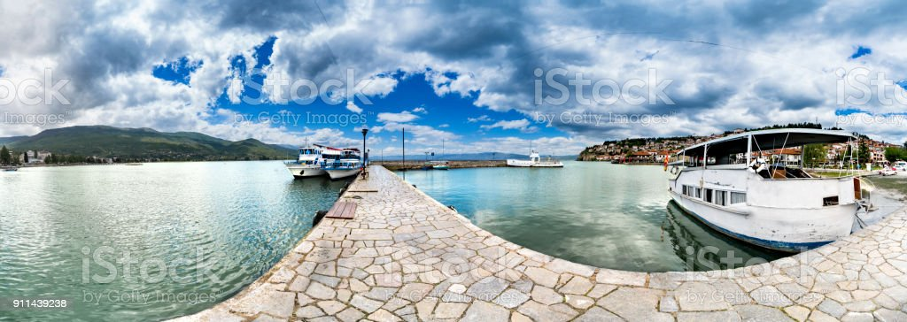 Panorama of Ohrid city and lake with waving Macedonian flag and several boats stock photo