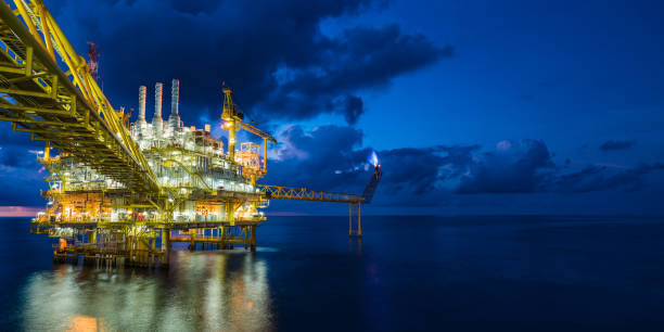 Panorama of oil and gas central processing platform in sun set where produced, treat the hydrocarbon then sent to refinery , petrochemical , power generation plant and tanker barge for export. stock photo