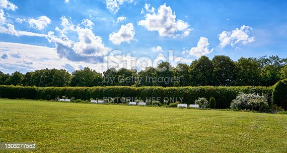 Schwerin, Germany - June 16, 2019: Panorama of park benches under a blue sky with sun and white clouds.