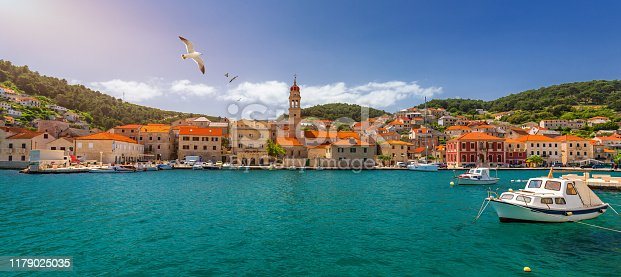 Panorama of picturesque town Pucisca in Croatia, Island Brac, Europe. Pucisca town mediterranean panorama with seagull's flying over the town. Croatia, Island Brac, Europe.