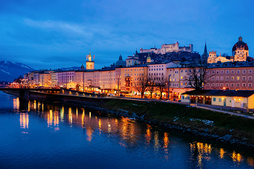 Panorama of Salzburg Hohensalzburg castle and Salzach River in Austria in evening. Landscape and cityscape of fortress in Mozart city in Europe at winter at night. View of old Austrian town