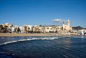 Sitges, Spain - June 6, 2017: People sunbathing on the Sitges beach in Spain