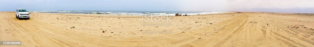 Waters edge, Skeleton Coast National Park, Namibia, Africa. Panoramic wide angle view of coastline of Skeleton Coast with a solitary vehicle driving on the treacherous sands along this notorious coastline famous for wrecking ships due to the dangerous Benguela current and fog