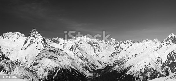 Panorama of snow covered mountain peaks. Caucasus Mountains in winter, region Dombay. Black and white toned landscape.