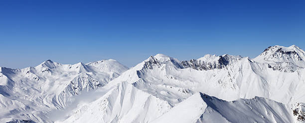 panorama of snow mountains and blue sky - snowy mountains stock photos and pictures