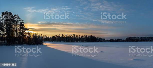 Photo of Panorama of sunrise over snow-covered lake in northern Sweden.