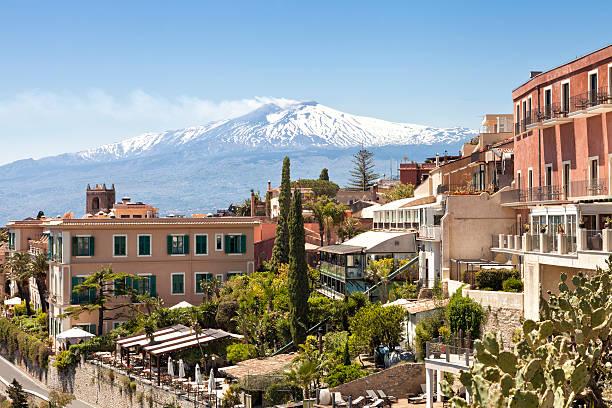 panorama of taormina with white peak of smoking volcano etna - 陶爾米納 個照片及圖片檔