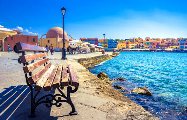 Panorama of the beautiful old harbor of Chania with the amazing lighthouse, mosque, venetian shipyards, Crete, Greece. stock photo