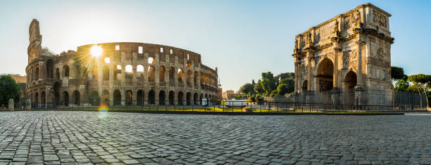 Panorama of the Colosseum (Coliseum) and the Arch of Constantine in the city center of Rome in Italy Panoramic view over the Colosseum (Coliseum) and the Arch of Constantine in the city center of Rome in Italy palatine hill rome stock pictures, royalty-free photos & images