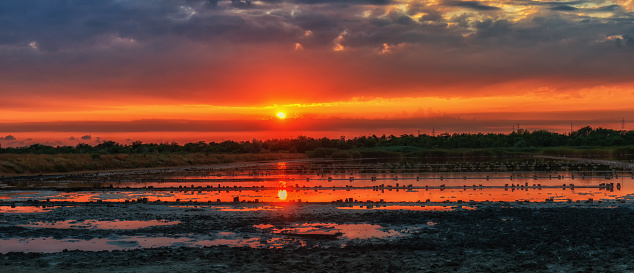Dawn over the developed salty and therapeutic mud lake. The water reflects the sky and the sun