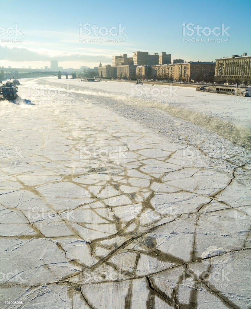 Panorama of the frozen, covered with ice floes Moscow River and Frunze Embankment, on the background the Ministry of Defence and the Pushkin bridge, back lit photo in cold sunny winter day stock photo