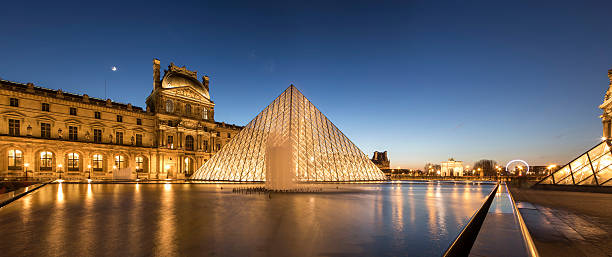 Panorama of the iconic Louvre Museum in Paris at sunset Paris, France - December 3, 2016: The Louvre Museum is one of the most important monument in the World and the new modern glass style pyramid that was built in the 1980s by late French president Mitterrand, stands in the middle of courtyard. musee du louvre stock pictures, royalty-free photos & images