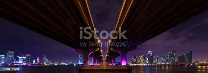 The MacArthur Causeway from below, going to Miami Beach, shoot at night with the city skyline and the Downtown - Brickell and Biscayne skyline in the background