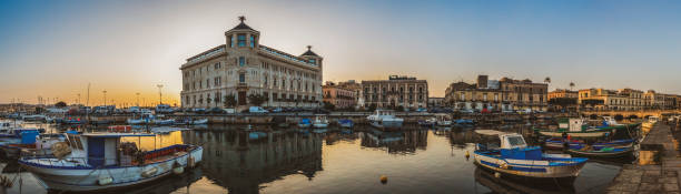 panorama der insel ortigia und desmeerhafen mit booten auf dem wasser bei sonnenaufgang in der nähe der stadt siracusa in sizilien, süditalien - ortygia stock-fotos und bilder