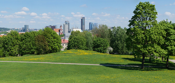 VILNIUS, LITHUANIA - MAY 12, 2016: Panorama of the spring sunny public garden on top of the old historical Lithuanian Tauras mountain. Are well visible  business areas of the city and and Saint Jacob's church
