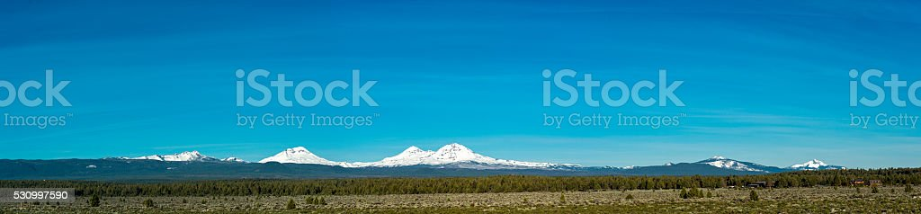Panorama of Three Sisters Mountains Oregon Snow Trees Blue Sky stock photo