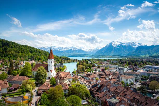 panorama of thun city  in the canton of bern with alps and thunersee lake, switzerland. - швейцария стоковые фото и изображения