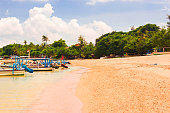 Panorama of Traditional Colorful Balinese Fishing Boats at the Beach of Sanur, Indonesia . Beautiful Tropical Beach Of Indonesia with Spider Boats and Tropical Trees.