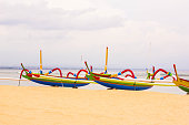Panorama of Traditional Colorful Balinese Fishing Boats at the Beach of Sanur, Indonesia . Beautiful Tropical Beach Of Indonesia with Spider Boats. Tropical Summer Concept Background.