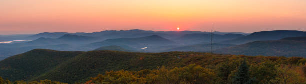 Panorama of warm golden sunlight shining across layers of rolling mountains during sunset. Overlook Mountain, NY