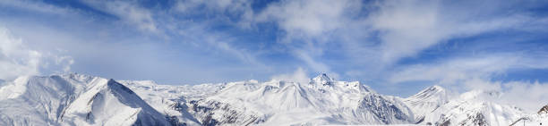 Panorama of winter snowy mountains and blue sky with sunlit clouds - foto stock