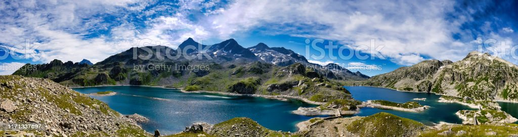 "Panorama on the 7 laux lakes and the summits around it The refuge of the ""7 laux"" is situated between the last lakes and is a real place of heaven. The ""Rocher blanc"" which is on the photography is the second highest summit of Belledonne. 360-Degree View Stock Photo"
