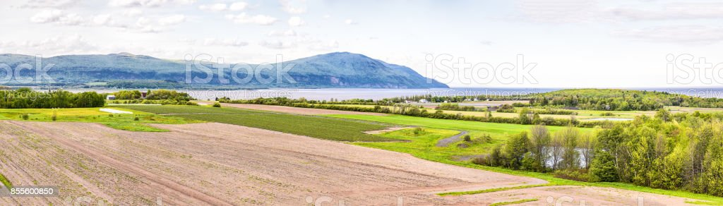 Panorama, panoramic aerial view of farmland in Ile D'Orleans, Quebec, Canada, plowed field, furrows, land, farm, house, barn, shed, Saint Lawrence river, hills, mountains and distant village stock photo