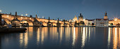 Panorama of the famous illuminated Charles Bridge (Karluv Most) reflecting in the Vltava River at Twilight. Edited Colors. Prague, Czech Republic, Europe.