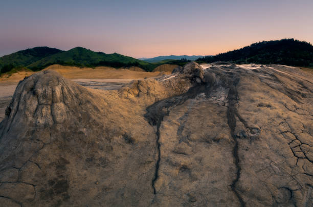 Panorama shot of some of the craters at Muddy Volcanoes in Romania, Buzau County with the mountains in the background against a clear sky stock photo