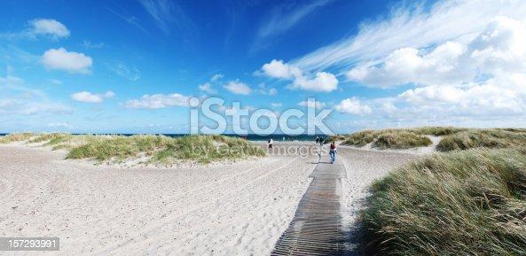People walking towards water on boardwalk at a beach in Skagen, Denmark.