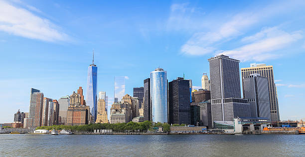 Panorama view of Manhattan Panorama view of Manhattan, New York City with blue sky and slightly cloud. Battery park on the edge of the shore which surround by many tall building in business area. manhattan financial district stock pictures, royalty-free photos & images