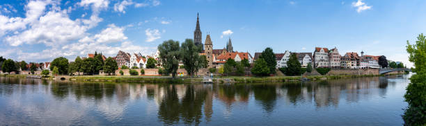 panorama view of the city of Ulm in southern Germany with the Danube River in front A panorama view of the city of Ulm in southern Germany with the Danube River in front ulm minster stock pictures, royalty-free photos & images