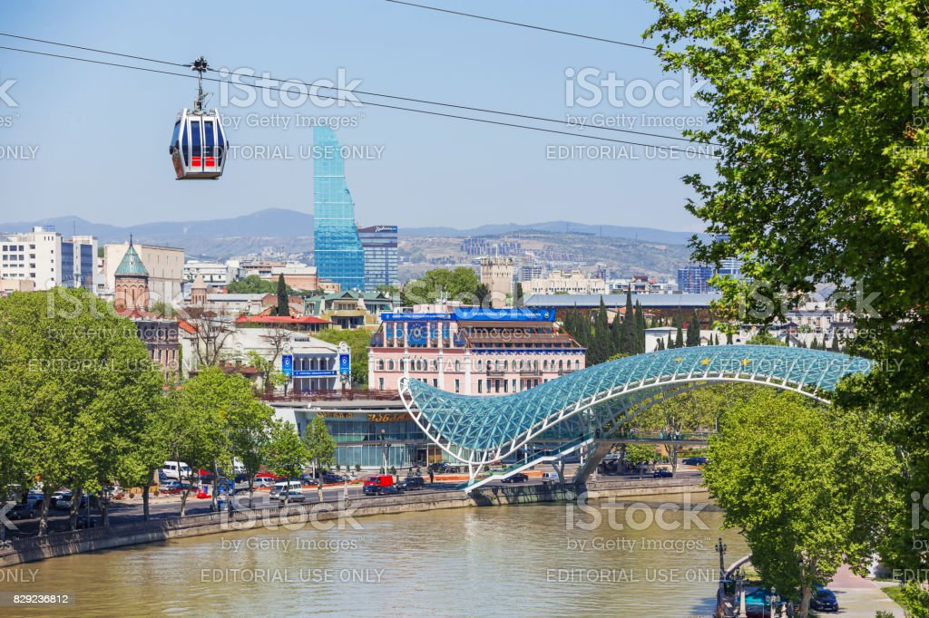 Panorama view on modern landmarks - Bridge of Peace and Biltmore Hotel Tbilisi. Cable road cabin gliding over the town. stock photo