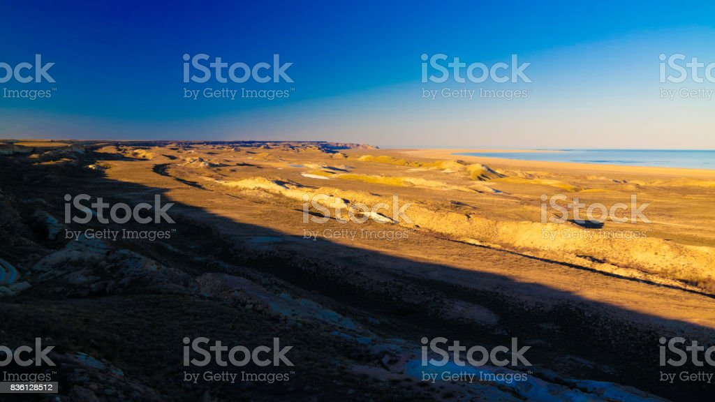 Panorama view to Aral sea from the rim of Plateau Ustyurt near Aktumsuk cape at sunset, Karakalpakstan, Uzbekistan stock photo