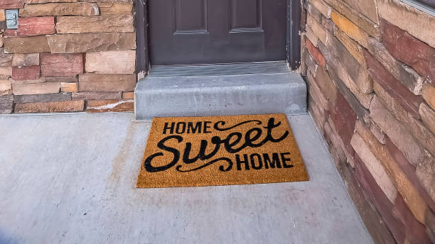 Panorama White wreath hanging on gray front door of home with a doormat by the doorstep stock photo