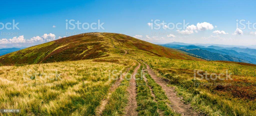panorama with dirt road through mountain ridge stock photo