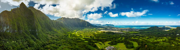 A Panoramic aerial image from the Pali Lookout on the island of Oahu in Hawaii.  With a bright green rainforest, vertical cliffs and vivid blue skies. stock photo