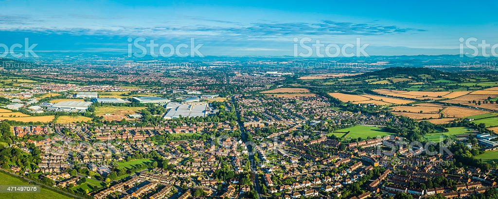 Panoramic aerial photo over suburban homes surrounded by green countryside stock photo