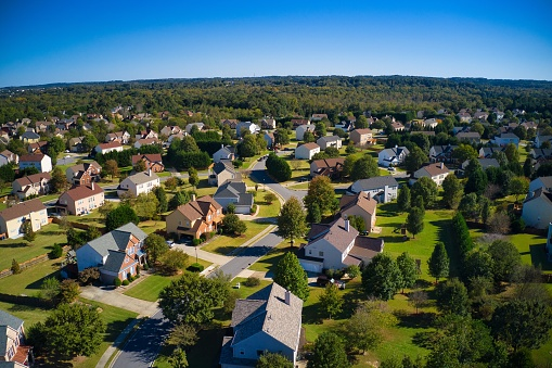 Shot using a drone during the golden hour shows an upscale suburbs with gold course, lake, houses and roof tops