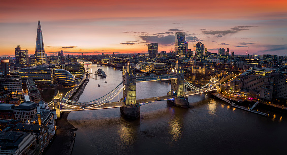 Panoramic, aerial view to the cityscape of London with Tower Bridge and the illuminated skyscrapers of the city during dusk, United Kingdom