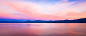 Panoramic background with brilliant colorful sky reflecting off the water at sunset with mountains at the horizon