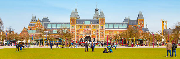 Panoramic banner background of Museumplein, Rijksmuseum, Holland Amsterdam, Netherlands - March 31, 2016: Panoramic banner background with people, grass field and view of Rijksmuseum, Museumplein museumplein stock pictures, royalty-free photos & images