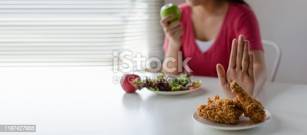 istock panoramic banner. Diet. young pretty woman refuse fried chicken, junk food or unhealthy food and eating fresh green apple salad for good health at home, weight loss, healthy food and dieting concept 1167427953