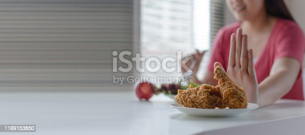 istock panoramic banner. Diet. young pretty woman refuse fried chicken, junk food or unhealthy food and eating fresh vegetables salad for good health at home, weight loss, healthy food and dieting concept 1169153850